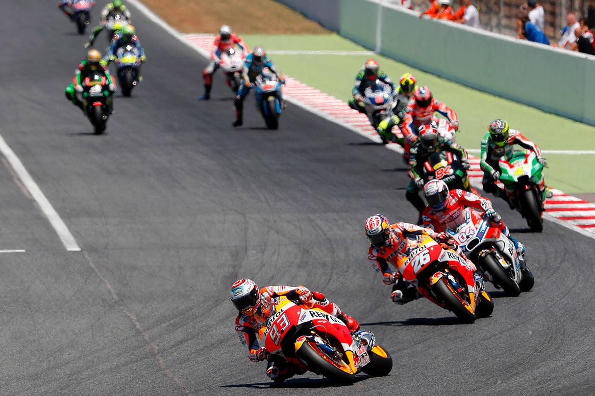 Pilotos de MotoGP en pista frenando antes de curva