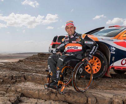 Isidre Esteve con su coche de rally en formación rocosa
