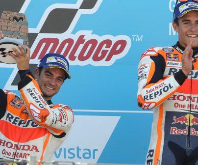Marc y Dani en el podio con Dani alzando un trofeo con forma de muro