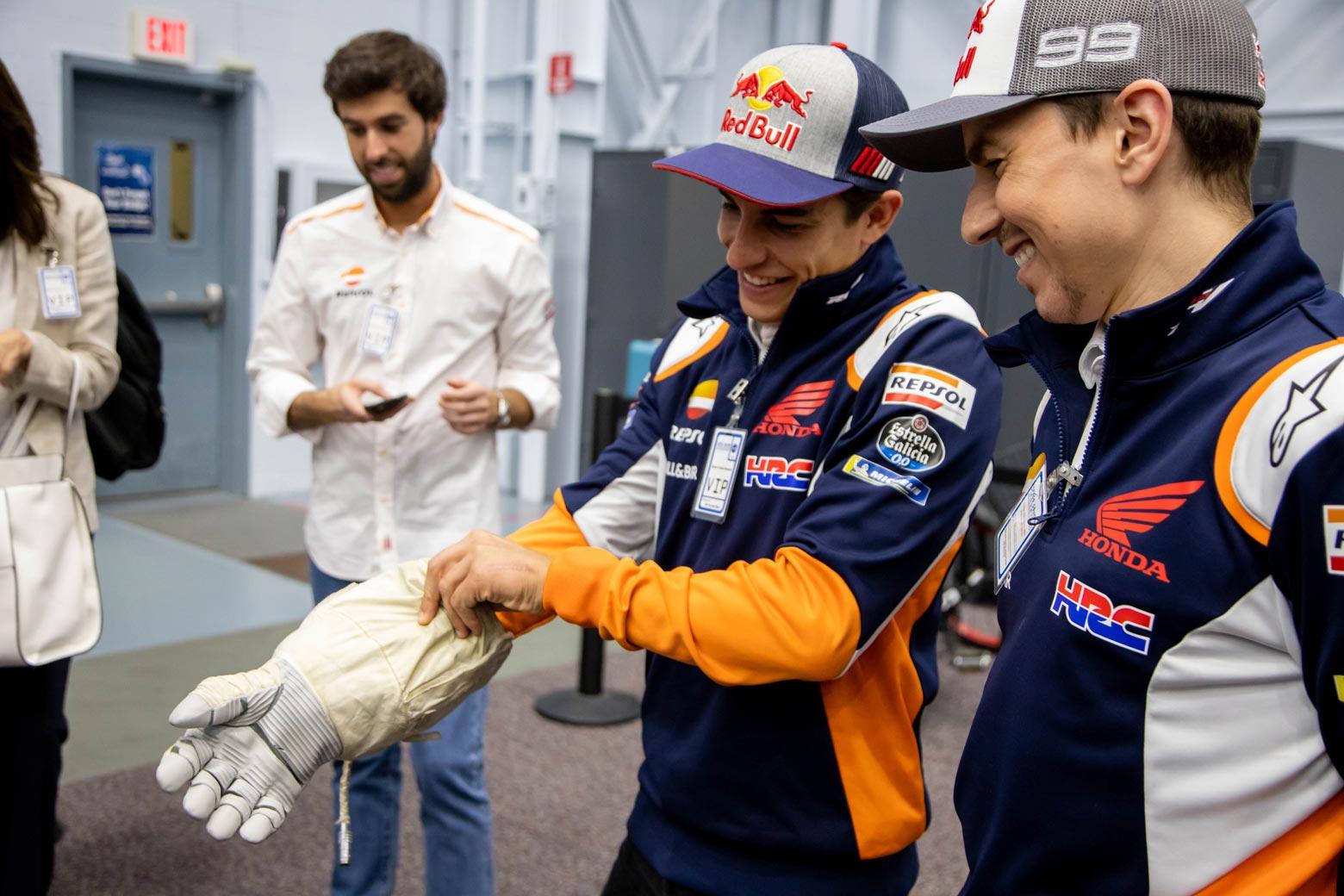Marc Márquez probandose un guante de astronauta mientras Lorenzo mira