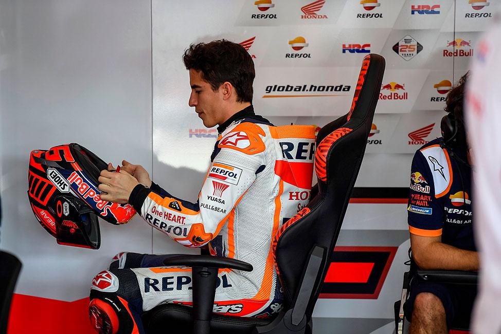 Márquez sentado poniéndose el casco