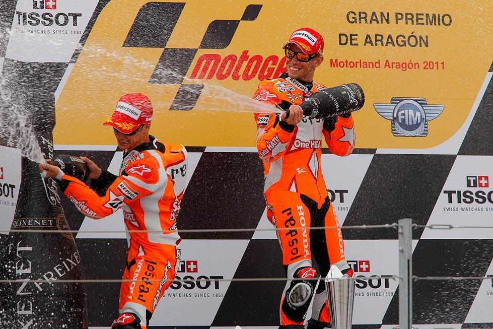 Casey Stoner y Dani Pedrosa en podio con diseño especial lanzando champán