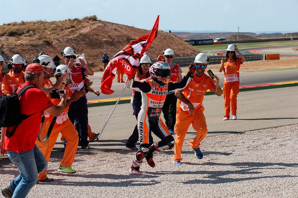 Marc Márquez celebrando con su bandera del 93 y los comisarios de pista