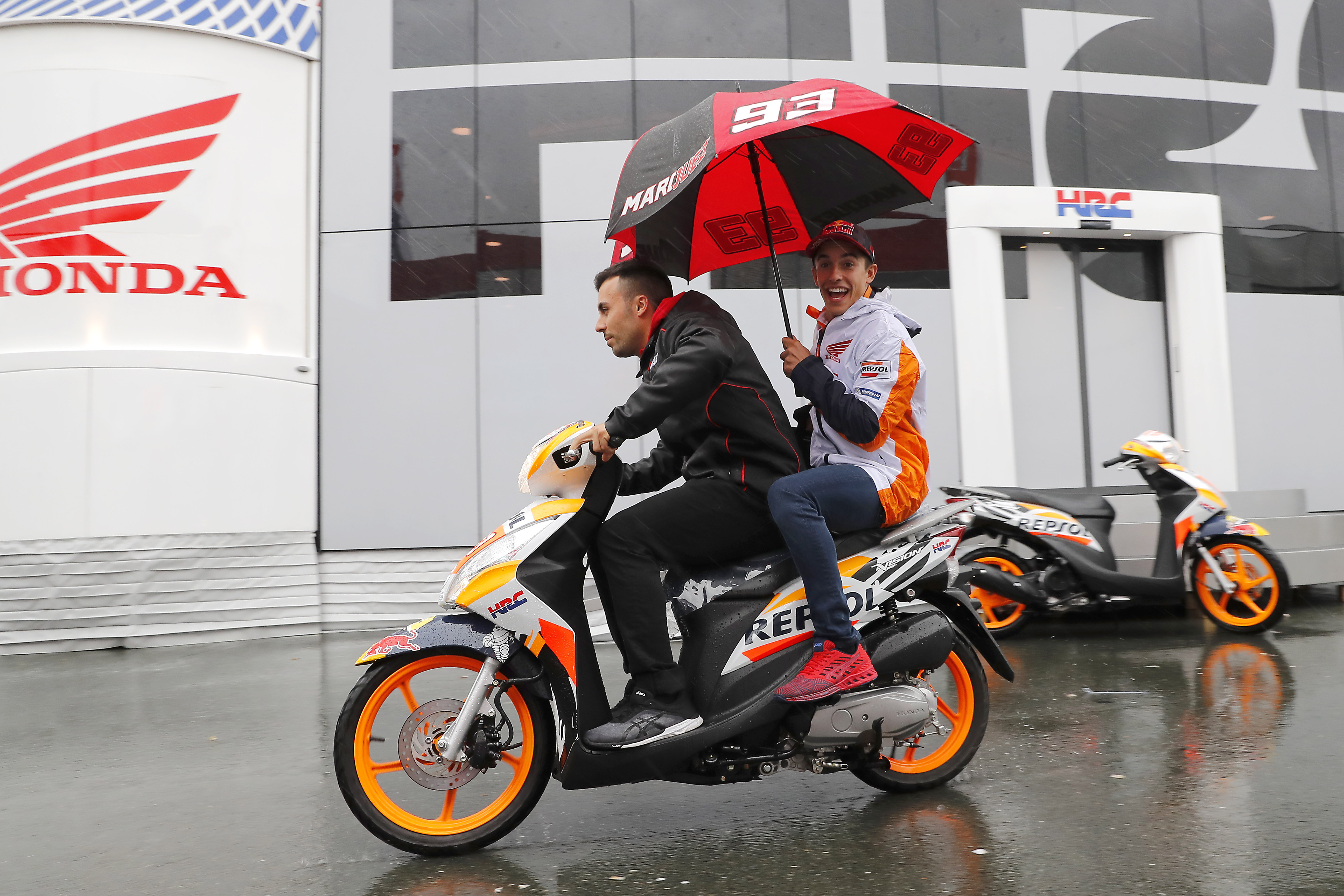 Marc Márquez sonriendo con paraguas en moto scooter