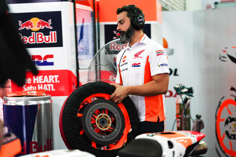 Un mecánico llevando un conjunto de llanta, neumático y disco