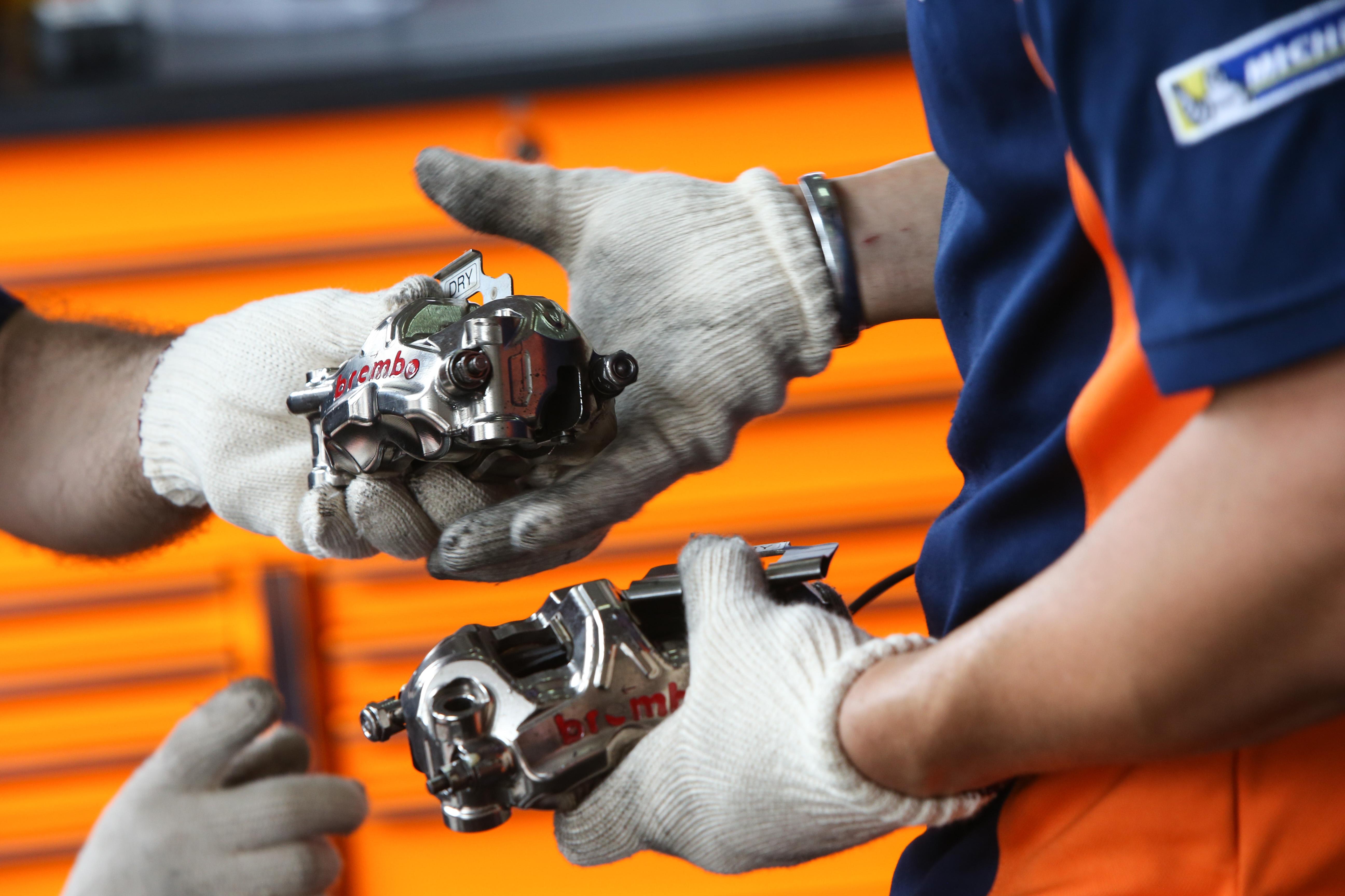 Pinzas de freno frontales RC213V en manos de mecánicos del Box Repsol
