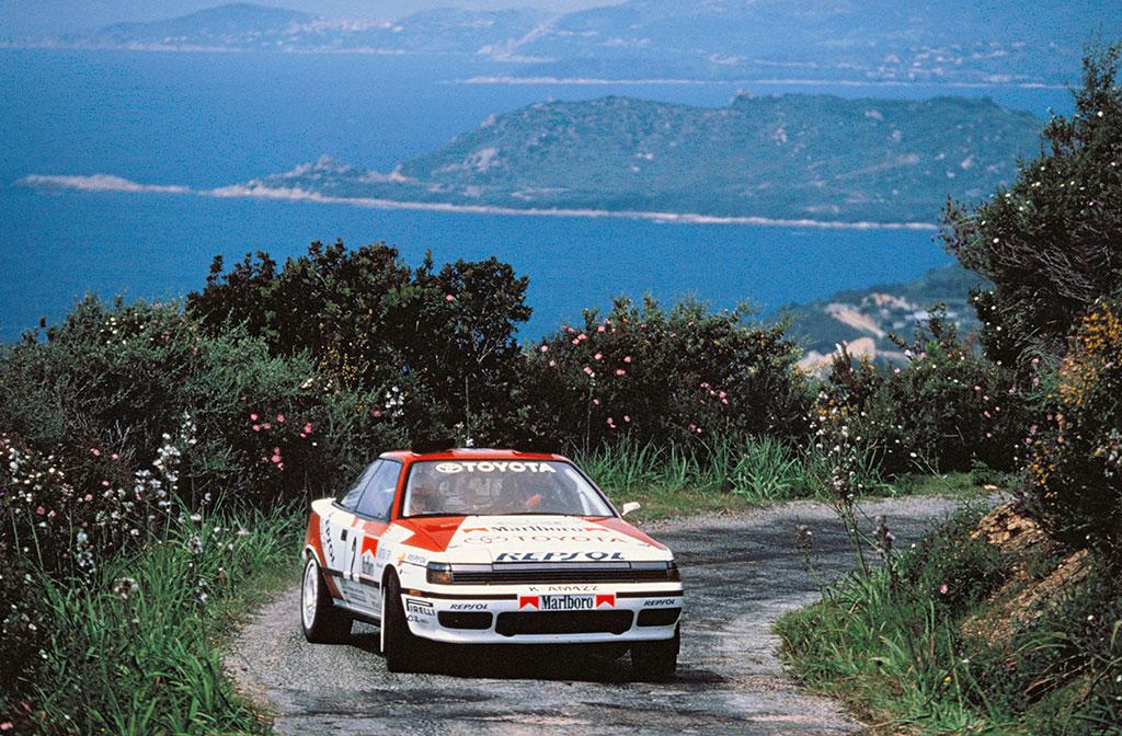 Carlos Sainz tomando una curva con la isla de Córcega de fondo