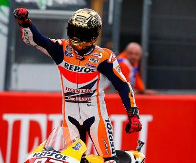 Marc Márquez con casco dorado levantado sobre la moto