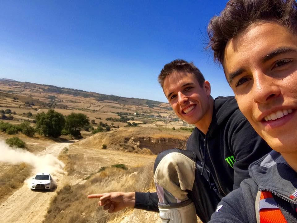 Álex Márquez, junto a su hermano Marc, señala un coche conduciendo en tierra