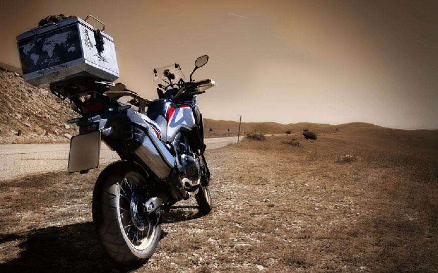 Una Africa Twin vista desde atrás con una gran maleta que muestra un mapa del mundo y un logo del Dakar