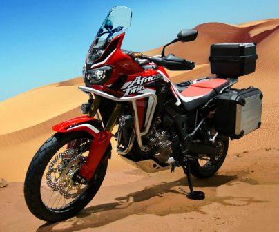 Una Honda Africa Twin de lado con dunas dunas de fondo en el desierto