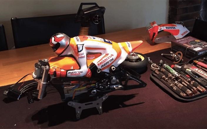 Encima de una mesa vemos la parte superior de una moto de radiocontrol de Marc Márquez