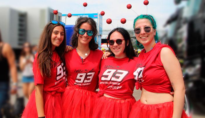 Un grupo de 4 amigas con camisetas de Marc Márquez, tutús rojos y antenas de hormiga posan
