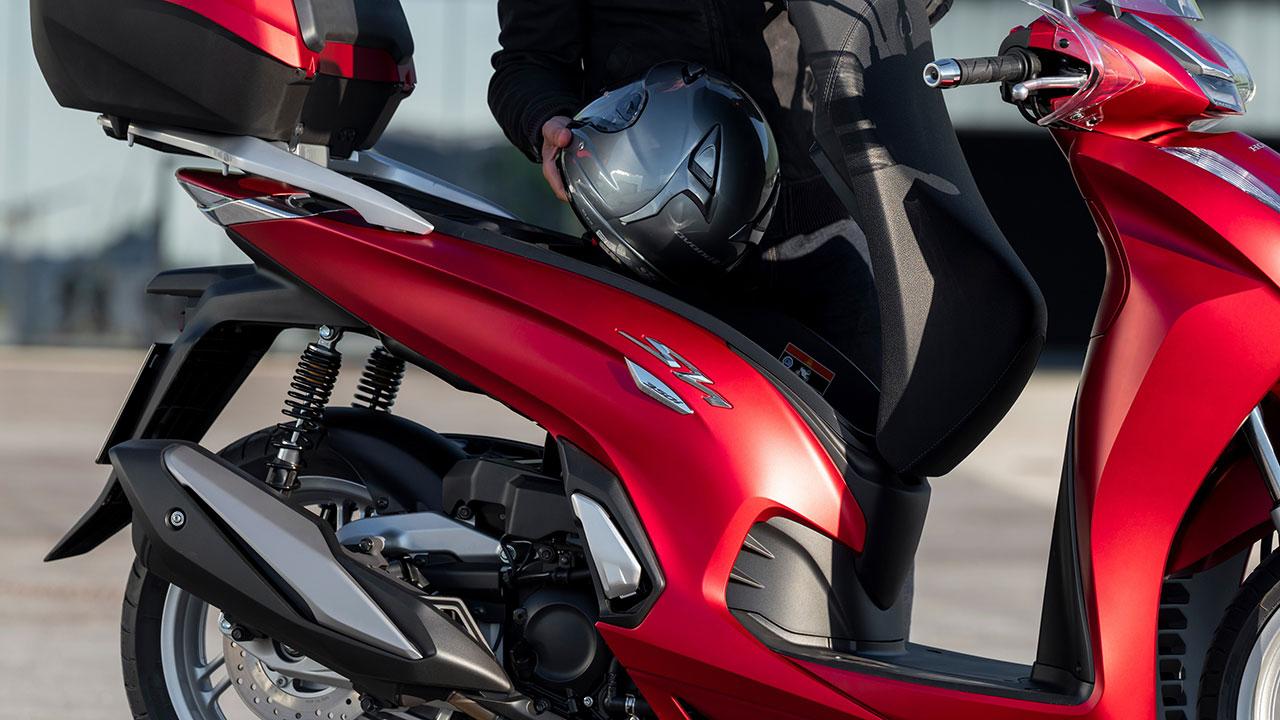 Motero guardando casco en el cofre de una Honda SH350i