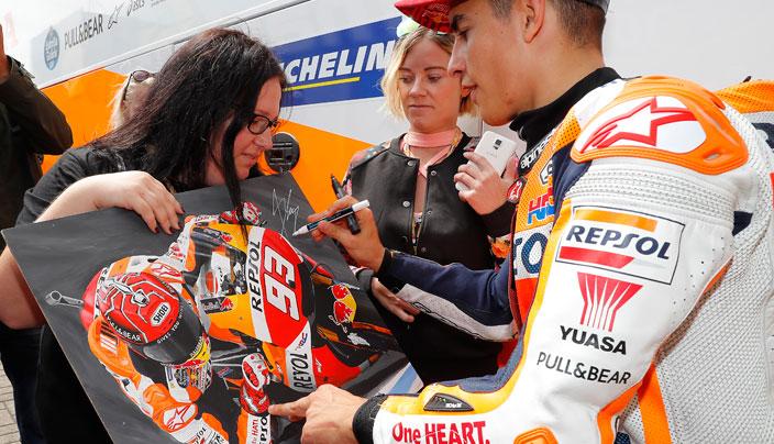 Una fan sostiene una ilustración de Marc Márquez mientras el piloto se la firma