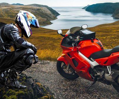 Un motorista de cuclillas junto a su moto en la montaña con todo el equipo ya que es un motero ATGATT