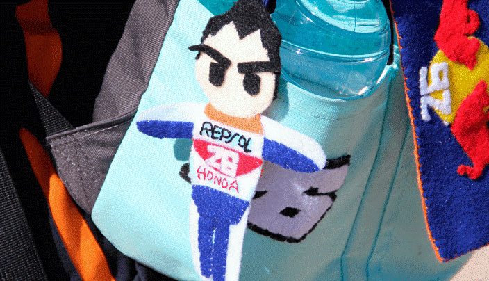 Foto lateral de una mochila con muñeco colgante de Dani Pedrosa