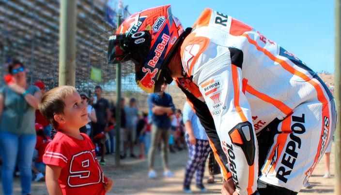 Fan totalmente euipado con mono y casco de Márquez conversa con un niño fan del piloto