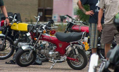 Varias motos Honda aparacadas en la calle con gente alrededor