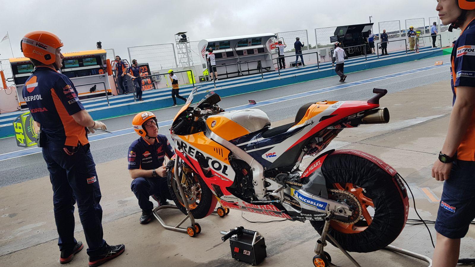 Técnicos de Repsol Honda en el pit lane preparando la moto