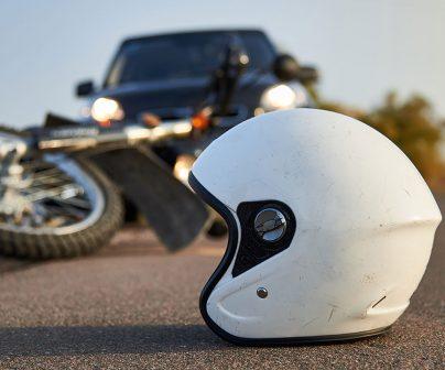 Un casco en el suelo junto a una moto caída. Seguros para moto.