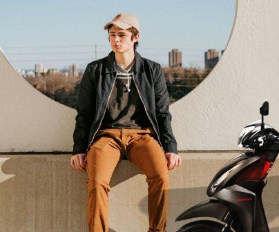 joven junto a su primera moto de 50 cc