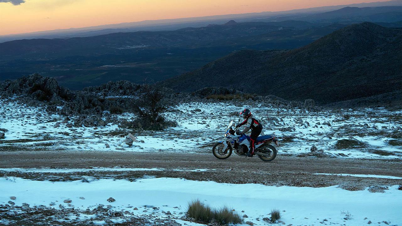Piloto con una Africa Twin por una pista con nieve
