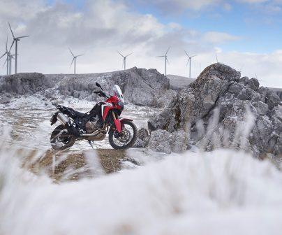 Honda Africa Twin en un paisaje nevado con molínos eólicos