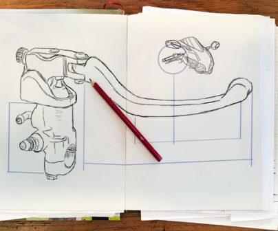 Esbozo a lápiz de una maneta de freno con bomba radial en papel sobre una mesa de madera