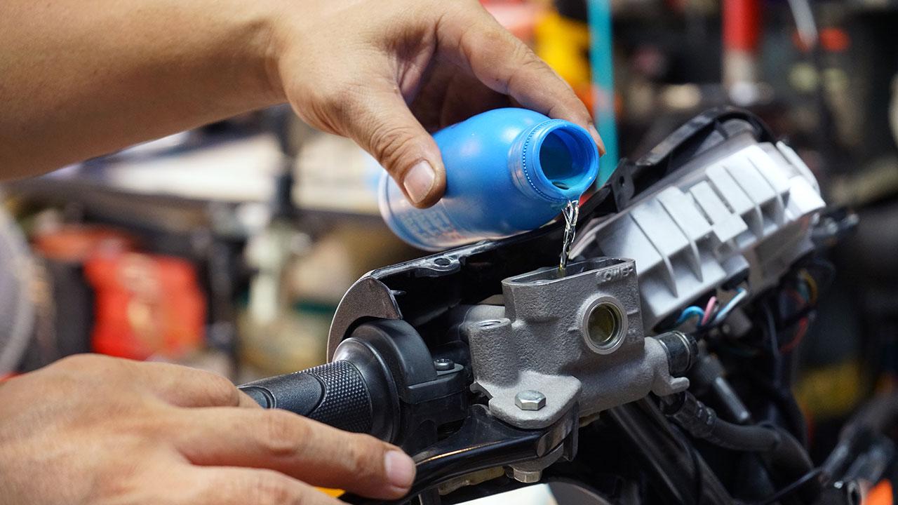 Añadiendo líquido de frenos al depósito de una moto