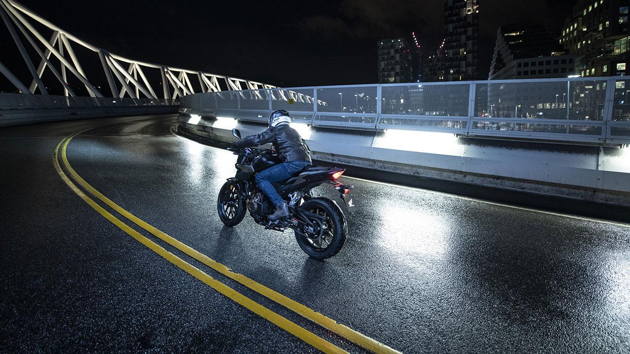 Piloto llevando una moto por una carretera mojada
