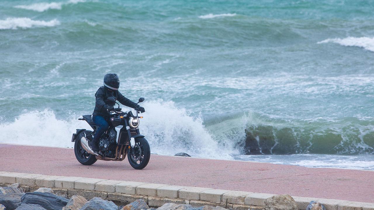 Piloto llevando una moto en una zona con viento