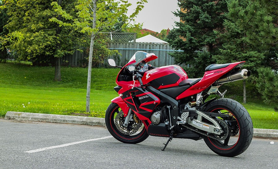 Una Honda CBR 1000RR Fireblade roja y negra aparcada en la calle frente a un parque
