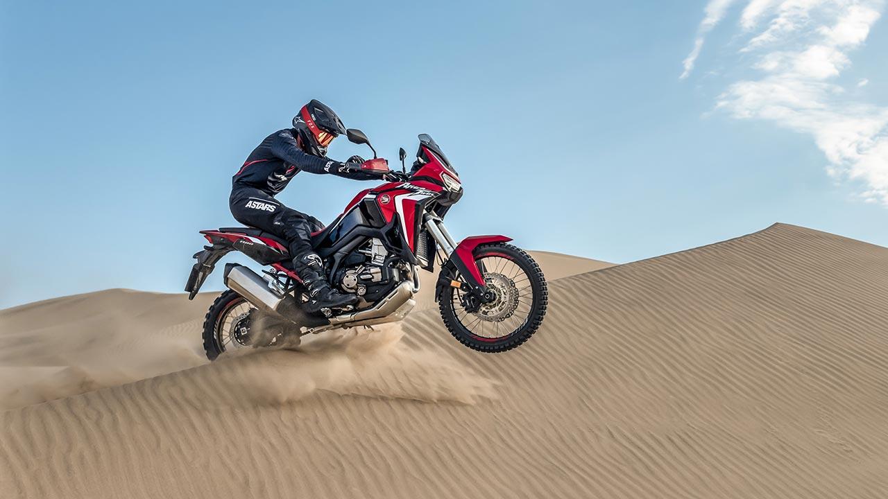 Motero sobre una Honda África Twin 2021 saltando sobre una duna