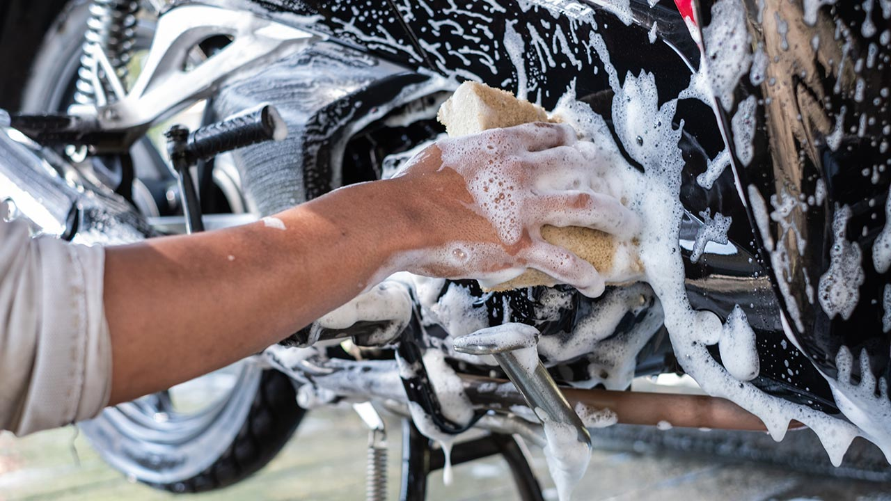 cómo lavar una moto, esponja y agua jabonosa