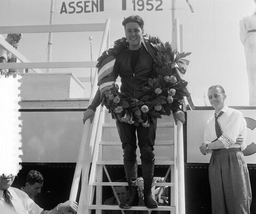 Geoff Duke con una corona de laurel al cuello tras competir en el circuito de Assen