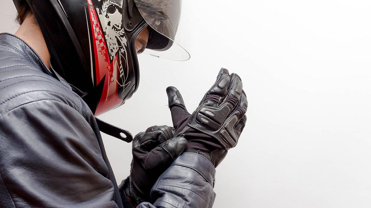 motero colocandose unos guantes como parte del equipamiento para ir en moto