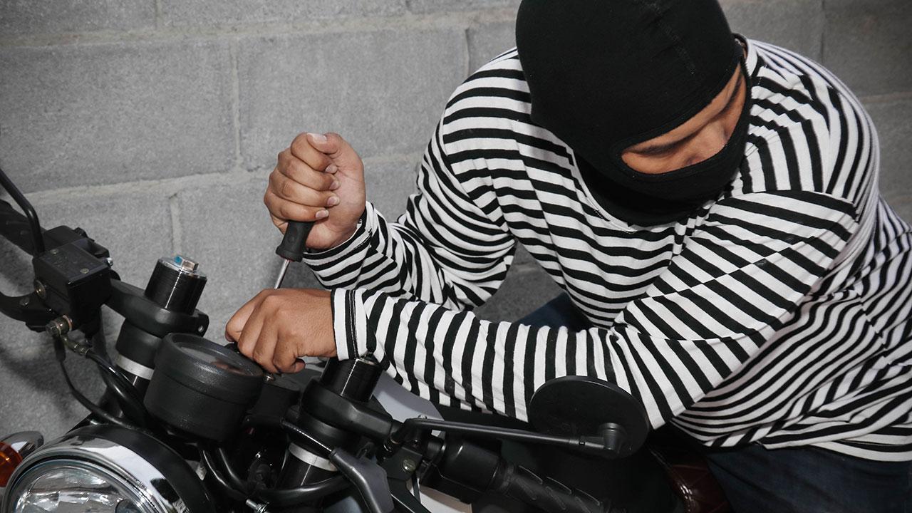 ladrón intentando robar una moto