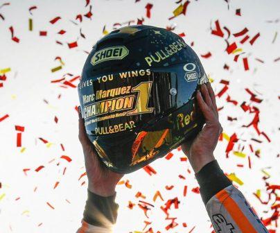 Las manos de marc levantan el casco de campeón rodeado de confetti naranja y rojo