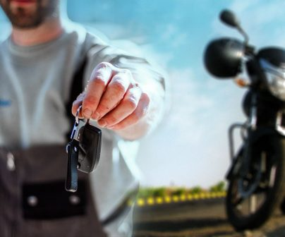 hombre con el brazo extendido ofrece a cámara las llaves de una moto naked que vemos aparcada en segundo plano