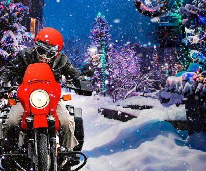 Motero conduce su moto navidenya en medio de una ciudad nevada