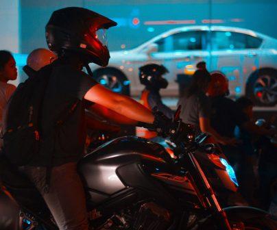 Motorista de perfil circula en su moto de noche con un escaparate detrás de él