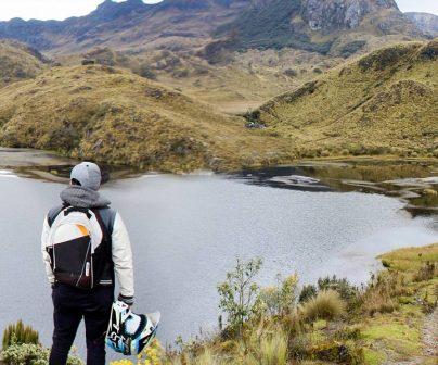 Motero mira las mágnificas vistas naturales de un lago