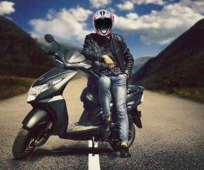 un motero posando con su nueva Honda de 125cc