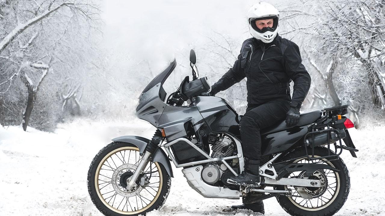 Motero en su moto en la nieve con equipamiento para el frío en moto