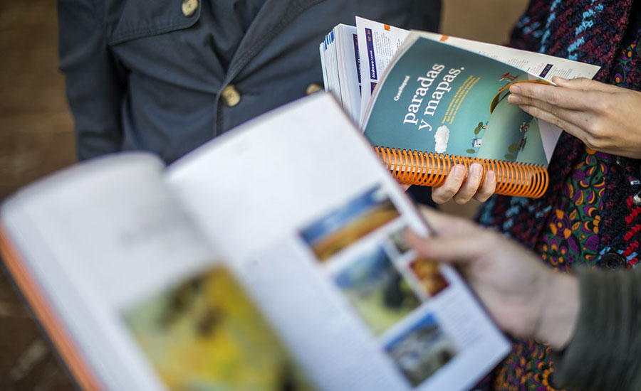 manos de moteros sostienen la guía Repsol mientras preparan su viaje a Pingüinos 2019
