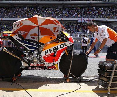 Mecánico junto a moto con calentadores de neumáticos de motogp en el pitlane