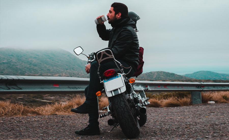 motorista bien abrigado disfruta de un café al lado de la carretera