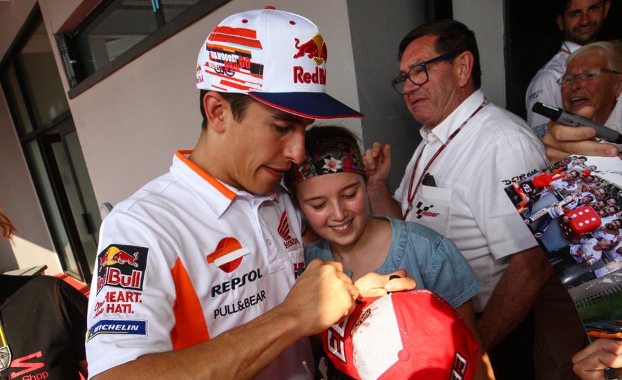 Marc Márquez firma la gorra a una fna en un Gran Premio de MotoGP