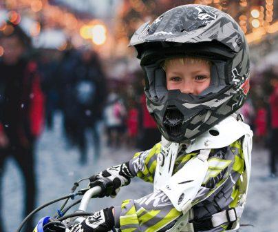 Niño con casco y mono de motocross en un ambiente navideño